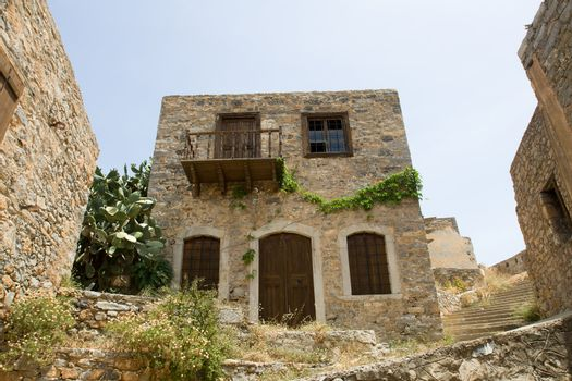 Picturesque old Mediterranean style abandoned lopsided rustic stone house with wooden sun blind, balcony in ancient town