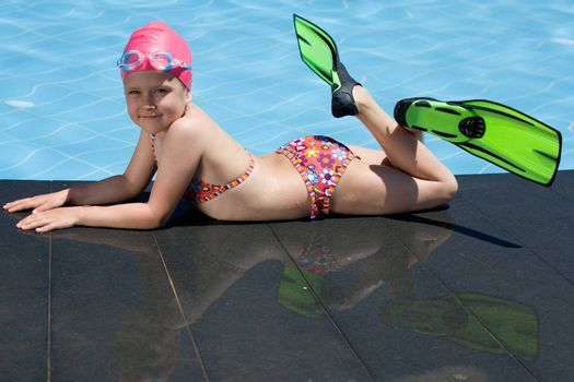 Smiling cute little child in bathing cap, glasses and fins is lying on the swimming pool ledge