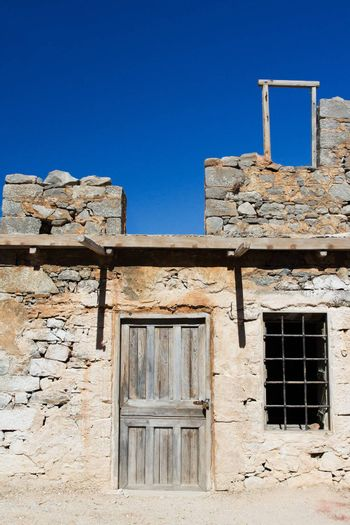 Picturesque old Mediterranean style abandoned lopsided rustic stone house with padlocked wooden door and window lattice on blue sky background