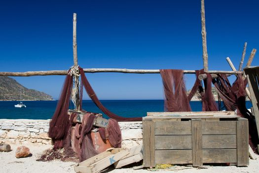 Picturesque marine landscape: drying fishing net, wooden chest on the background of blue sea, sky and mountain