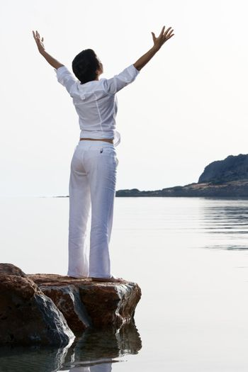 Young dressed white woman with raised arms meets sunrise staying barefoot on the sea stone. Back lighting