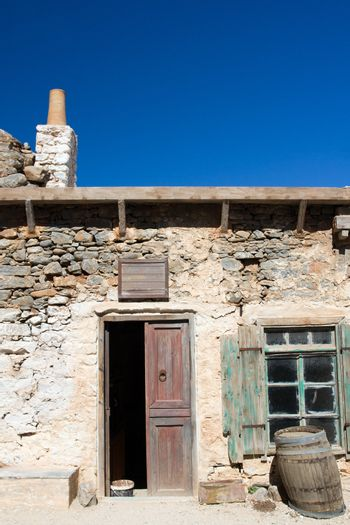 Picturesque old Mediterranean style abandoned lopsided rustic stone coffee house with opened wooden sun blind, chimney,  doorway, wine barrel and bench on the blue sky background