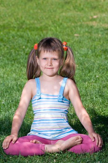 Smiling happy little cute girl who is sitting and meditating in yoga lotus asana under tree shadow on the green grass