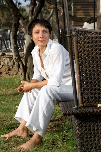 Young barefoot relaxing woman dressed white suit sits on wicker park bench