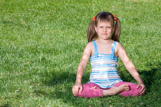 Cute little girl is sitting in yoga lotus asana under tree shadow on the green grass