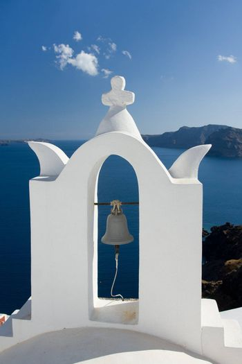 See view and cloudy sky through traditional white church arch and bell in village Oia of Cyclades Island Santorini Greece