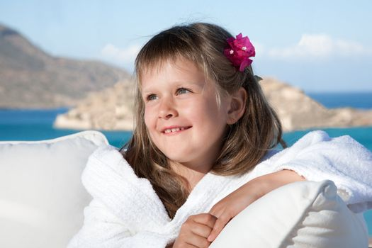 Portrait of happy smiling little girl with flowered hair in white bathrobe relaxing on terrace divan on the sea background
