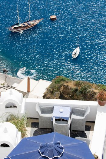 Sea view on moored yacht and sailboat as seen from the restaurant's terrace on cliff Santorini luxury island, Greece