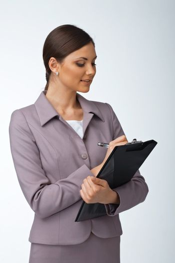 Portrait of a young business woman writing something on the folder with papers