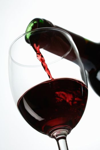 Red wine pour in a glass on white background