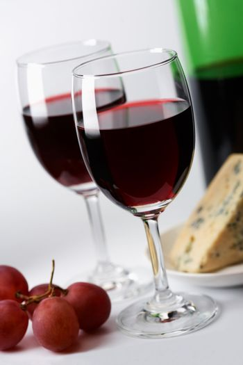 Red wine, grape  and cheese in the background