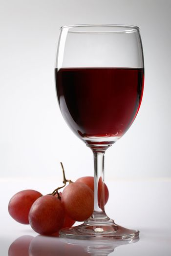 Grape and red wine on white background