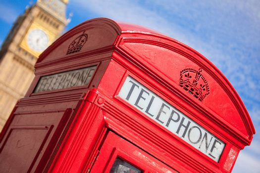 Main London symbols: red public telephone box and clock on Big Ben tower of Westminster Palace on cloudy sky background in Great Britain