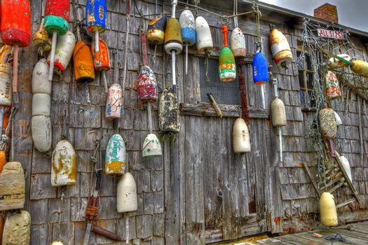 Series of lobster buoys hanging on the side of a boathouse