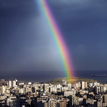 Bright rainbow over city