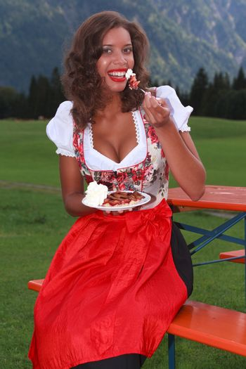 Young girl in traditional Bavarian costume eating a cake