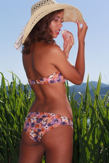 Young Brazilian woman in bikini with hat is a praline