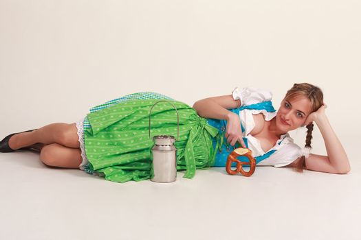 Bavarian girl in costume lying on the ground with biscuits and milk jug