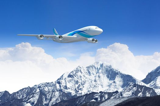 White passenger plane flying in the blue sky above the mountains with snow tops