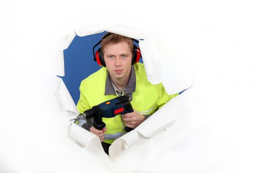 Worker with ear muffs and power drill