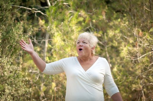 Elderly woman in a summer park .