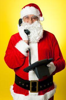 Smiling aged Santa attending phone call