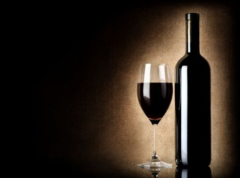 Wine bottle and wineglass on a old background