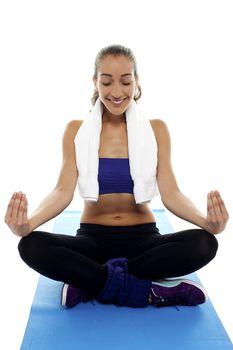 Attractive brunette meditating in lotus posture