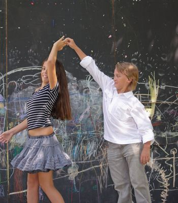 Portrait of of dancing boys and girls near a wall with graffiti.