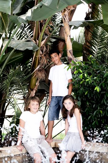 Portrait of three children near a fountain surrounded by tropical plants.