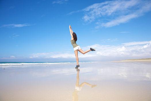 sportswoman stretching on seashore