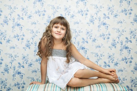 Portrait of sincere cheerful tender young blond girl child with grey eyes and wavy long hair in relaxed sitting posture looking at camera