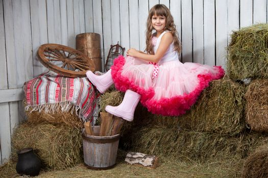 Portrait of funny little blond girl villager in rubber boots dressed luxuriant wavy ball dress with frill sitting on haystack  in wooden vintage hayloft