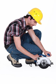 Man kneeling to use circular saw