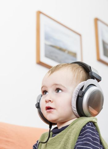 young child on couch with big earphone