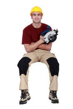 Man with circular saw sat on ledge