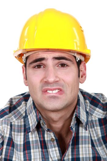 Builder with pained expression on face