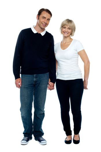 Middle aged couple posing with hand in hand