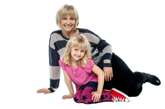 Cheerful mum and daughter sitting on studio floor