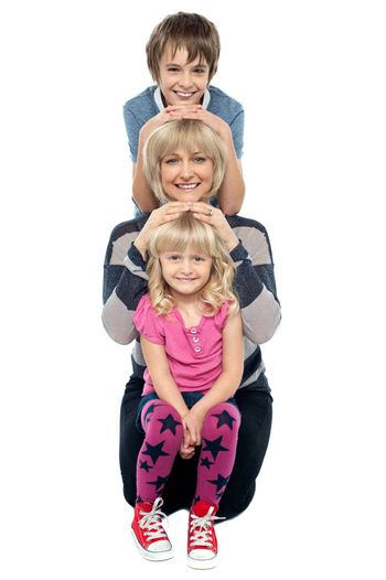 Mother posing with her adorable son and daughter. Studio shot over white.