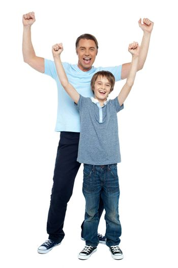 Father and son celebrating their success. Rejoicing with raised arms.