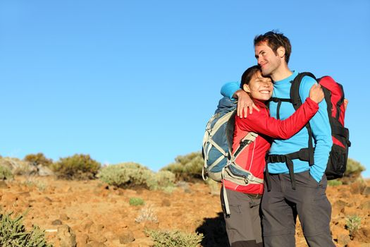 Happy couple healthy lifestyle affectionate outdoors in nature during hiking travel. Man and woman hikers smiling in mountain desert landscape.