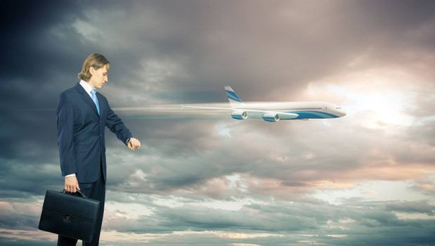 Businesman and plane on the background against cloudy sky