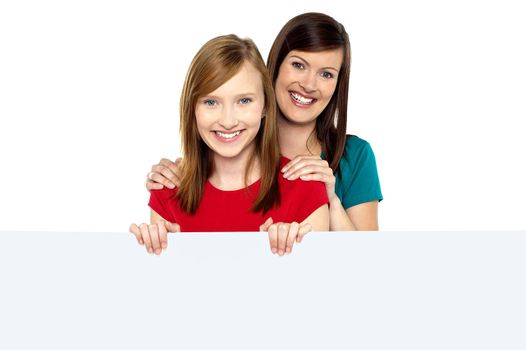 Girl holding ad board with her mother behind her