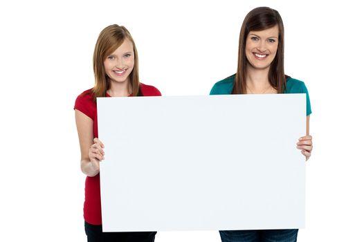 Gorgeous women presenting blank ad board