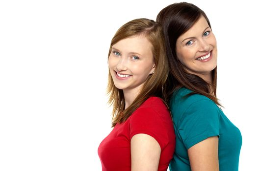 Joyous trendy mom and daughter standing back to back