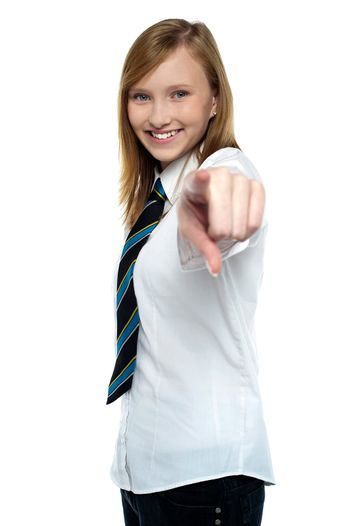 Cheerful young girl pointing towards the camera