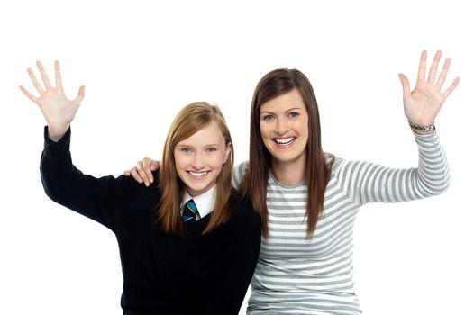 Mum and daughter waving hands at the camera