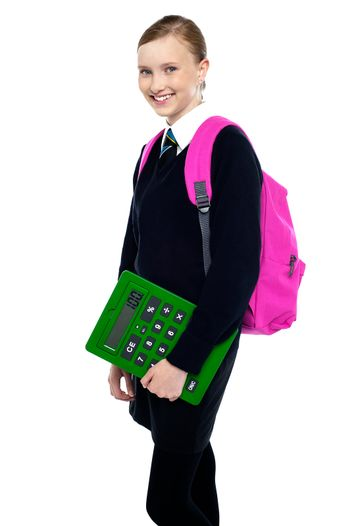 School girl posing with backpack and calculator