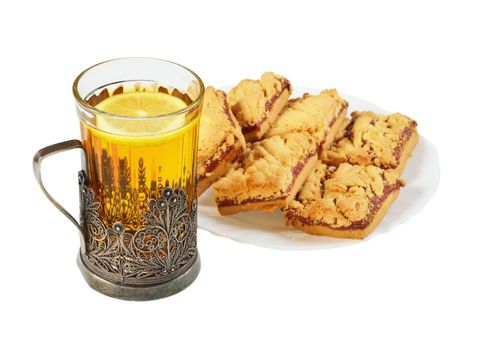 Tea in a glass in the cup holder and saucer with cookies.